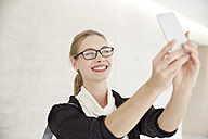 Smiling young woman with glasses taking a selfie - FMKF003065