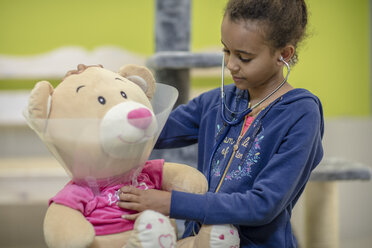 Girl playing veterinarian with teddy bear - ZEF009824