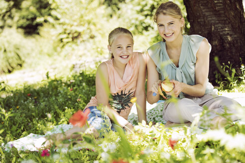 Portrait of smiling girl and young woman sitting together on blanket in a park - GDF001109
