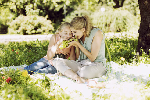 Girl and young woman sitting together on blanket in a park eating grapes - GDF001112