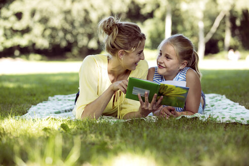 Girl and young woman with book lying on blanket in a park - GDF001115