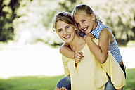 Portrait of happy young woman and girl in a park - GDF001121