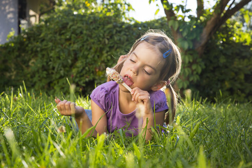 Little girl lying on meadow eating ice lolly - LVF005211