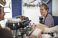 Young barista making coffee for customers - ZEF009842