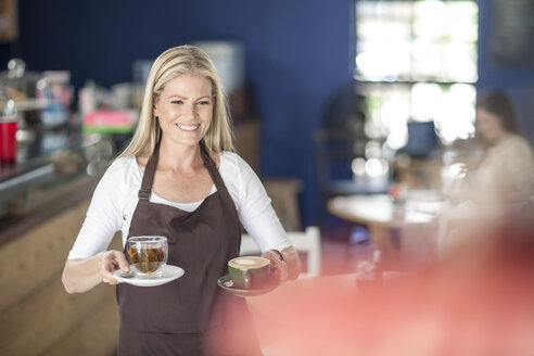 Waitress serving coffee and tea in a cafe - ZEF009857
