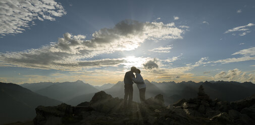 Happy couple kissing at sunset in the mountains - MKFF000331