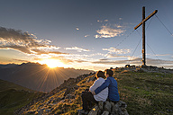 Happy couple watching sunset in the mountains - MKFF000334