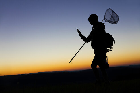 Female hiker carrying dip net and smart phone at dawn - MIDF000788