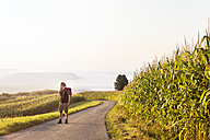Man hiking on street through cornfields - MIDF000794
