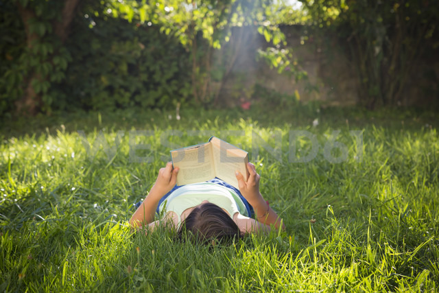 Girl reading book on a meadow - LVF005228