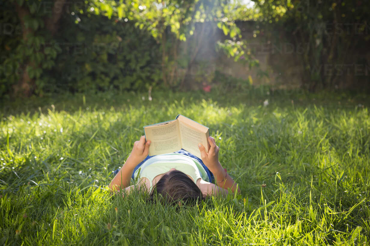 Girl reading book on a meadow - LVF005228 - Larissa Veronesi/Westend61