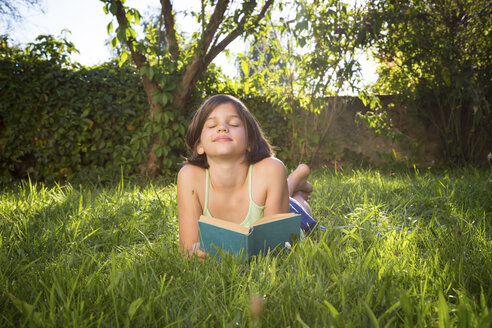 Happy girl lying on meadow with a book - LVF005231