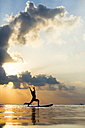 Thailand, man doing yoga on paddleboard at sunset, bridge position, warrior pose - SBOF000179