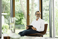 Smiling man with tablet sitting on chair in his living room - SBOF000182