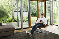 Man sitting with tablet on chair in his living room - SBOF000185