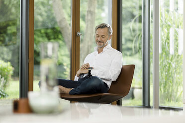 Man sitting on chair in his living room looking at smartwatch - SBOF000188