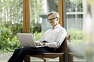 Smiling man sitting on chair in his living room using laptop - SBOF000194