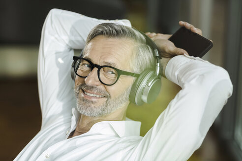 Portrait of smiling man with grey hair and beard listening music with headphones - SBOF000200