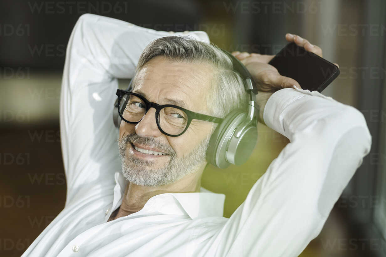 Portrait of smiling man with grey hair and beard listening music with headphones - SBOF000200 - Steve Brookland/Westend61