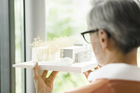 Back view of man looking at architectural model - SBOF000218