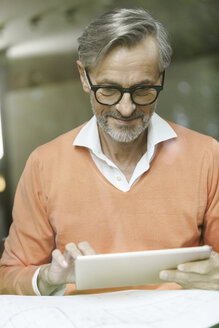 Man with construction plan using tablet - SBOF000221