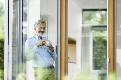 Smiling man with cup of coffee standing in his house looking through window - SBOF000230