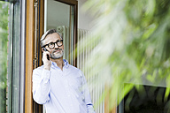 Man on the phone standing at open door of his house - SBOF000233