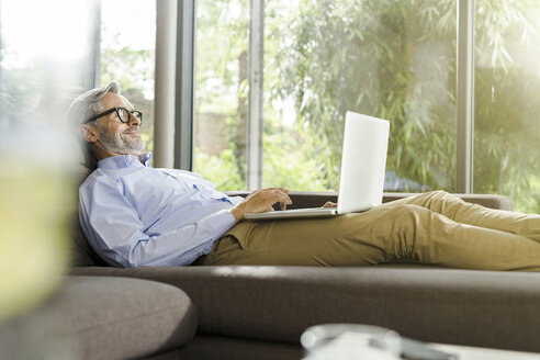 Smiling man lying on couch in his living room using laptop - SBOF000239