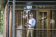 Man standing on balcony of his house looking at tablet - SBOF000248
