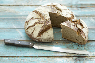 Rustic rye bread on blue wood, knife - MAEF011984