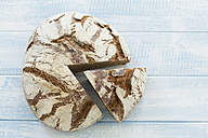 Rustic rye bread on blue wood - MAEF011987