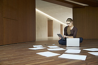 Young woman sitting on floor working with tablet and laptop - FMKF003084