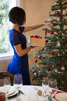 Woman decorating the Christmas tree - ABZF001038