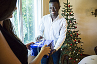 Man handing over Christmas present to woman - ABZF001041