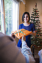 Woman handing over Christmas present to man - ABZF001044