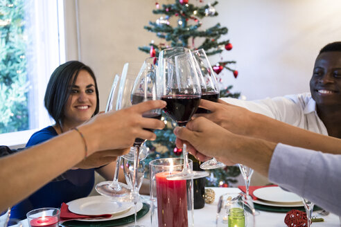 Friends toasting with wine during a Christmas dinner - ABZF001053