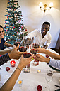 Friends toasting with wine during a Christmas dinner - ABZF001062