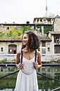 Italy, Milan, smiling young woman with backpack wearing white summer dress standing in front of water - MRAF000117