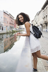 Italy, Milan, portrait of smiling young woman with backpack wearing white summer dress  leaning on railing - MRAF000120