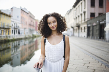 Italy, Milan, portrait of smiling young woman with curly brown hair - MRAF000123