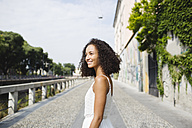 Portrait of smiling young woman with curly brown hair - MRAF000129