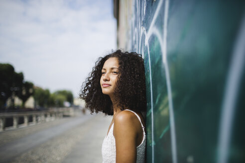 Portrait of young woman leaning against wall - MRAF000132