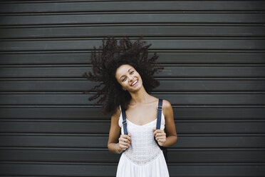Portrait of smiling young woman standing in front of roller shutter shaking her head - MRAF000135