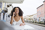 Portrait of smiling young woman on the phone at sidewalk cafe - MRAF000138