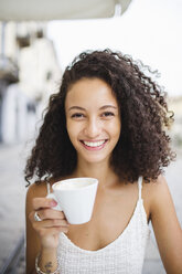 Portrait of happy young woman drinking coffee at sidewalk cafe - MRAF000144
