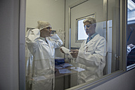 Two lab technicians putting on sterile protective clothing - ZEF010018