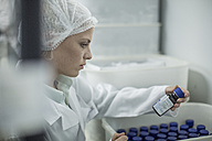 Lab worker in pharmaceutical plant looking at pill bottle - ZEF010039