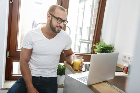 Gay man drinking orange juice while reading emails - MADF001167