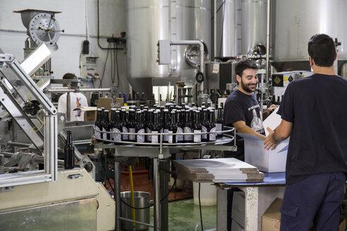 Men working in beer bottling plant - ABZF001087