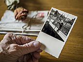 Old woman holding picture of her boyhood friend in hand, old letters and dried rose - EJWF000789